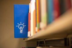 An idea icon on book in a bookshelf. An idea icon on a blue book in a bookshelf Royalty Free Stock Images