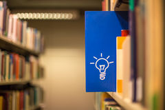 An idea icon on book in a bookshelf. An idea icon on a blue book in a bookshelf Stock Image