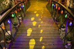Idea innovadora de los rastros del pie humano en el camino de madera con las luces coloridas que cuelgan en las verjas Gema ocult imagen de archivo