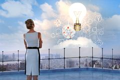 Idea and innovation concept. Back view of young woman looking at abstract business hologram and lamp on sky background while standing on balcony. Idea and Royalty Free Stock Image