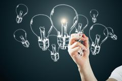 Idea, innovation and solution concept. Male hand drawing glowing lamps on dark bakcground. Idea, innovation and solution concept royalty free illustration