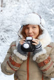 Idea inspired by the winter. Beautiful young woman in down jacket, fingerless mittens and hat with white fur looking sly and holding knitted camera at the Stock Photo
