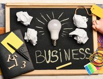 Idea lamp with business accessories on grey chalkboard. White lamp with paper, notebook, pen, chalk, piggy bank, numbers and elastics. Board with stationery on stock photos