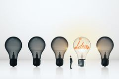 Idea and leadership concept. Tiny businessman looking at row of light bulbs with one illuminated. Idea and leadership concept royalty free stock image