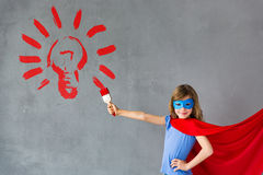 Idea light bulb. Happy child painting big red light bulb on the wall. Superhero kid playing at home. Home renovation and idea design concept royalty free stock photography