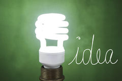 Idea On light Flourescent light bulb on green background. Idea word on a green background with a white flourescent light bulb besides it Stock Photography