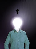 IDEA MAN. A human figure with a glowing bulb for a head stands in front of a dark keyhole Royalty Free Stock Photos