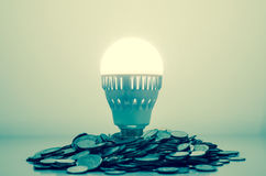 Idea is money concept, Light bulb bright on money coins pile Royalty Free Stock Photo