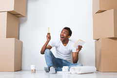 Idea. Moving. Joyful man sitting on the floor and decorations in the new house Stock Photos