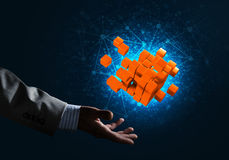 Idea of new technologies and integration presented by cube figure. Close of businessman hand holding cube figure as symbol of innovation, mixed media Stock Images