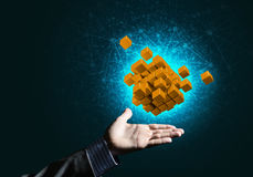 Idea of new technologies and integration presented by cube figure. Close of businessman hand holding cube figure as symbol of innovation, mixed media Royalty Free Stock Photography