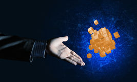 Idea of new technologies and integration presented by cube figure. Close of businessman hand holding cube figure as symbol of innovation, mixed media Royalty Free Stock Photo