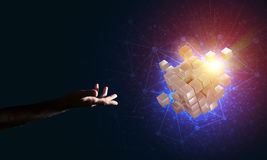 Idea of new technologies and integration presented by cube figure. Close of man hand holding cube figure as symbol of innovation. Mixed media Royalty Free Stock Image