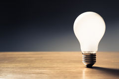Idea. One white light bulb glowing on the table stock photo