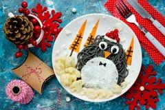 Idea para los niños - spagehetti negro del arte de la comida de la diversión del pingüino con frito Foto de archivo libre de regalías