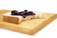 Idea per la foto della prima colazione A del morso da una fetta di pane integrale bianco con il mirtillo, l'inceppamento del mirt fotografie stock