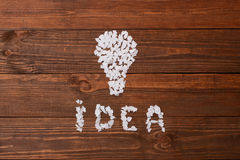 Idea. Pieces of paper on the table in the shape of lamp. Redwood Stock Photography