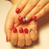 The idea for a red manicure with a pattern. Nail extension, gel Polish. Short round nails covered with red lacquer cherry color, matte finish. Beautiful simple royalty free stock images