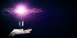Idea and science concept. Hand holding creative glowing lamp on dark background. Idea and science concept royalty free stock photography