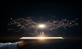 Idea and science concept. Hand holding tablet with creative glowing lamp on dark background. Idea and science concept stock images