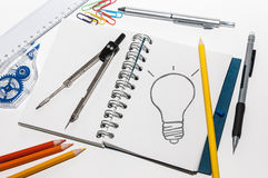 Idea. Several objets office and a notebook with a drawing of a bulb Stock Photography