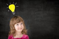 Idea. Smart kid in class. Happy child against blackboard. Drawing light bulb. Idea concept stock image
