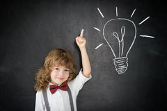 Idea. Smart kid in class. Happy child against blackboard. Drawing light bulb. Idea concept stock photo
