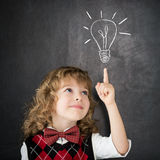 Idea. Smart kid in class. Happy child against blackboard. Drawing light bulb. Idea concept royalty free stock photography