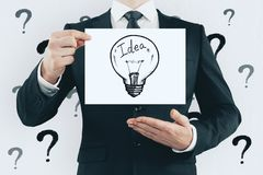 Idea, solution and presenation concept. Unrecognizable businessman holding creative light bulb sketch on white background with question marks. Idea, solution and stock photo