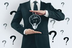 Idea, solution and workshop concept. Unrecognizable businessman holding creative light bulb sketch on white background with question marks. Idea, solution and stock images