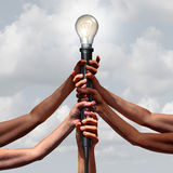 Idea Team Group. As diverse people holding an electric light socket with an illuminated lightbulb as a connected community insight or social thinking concept Royalty Free Stock Images