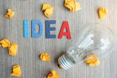 Idea TEXT on and crumbled paper with lightbulb on wooden table background. vision, Creative, Innovation, Imagination, inspiration royalty free stock photo