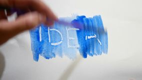 Idea text inscription watercolor artist paints blot isolated on white background. Art stock video footage