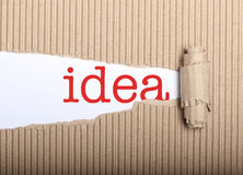 Idea text on paper and torn cardboard. Idea text on white paper with copy space and torn cardboard Stock Photography