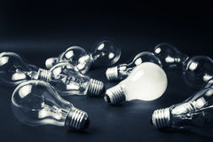 Idea to success. White light bulb glowing among the others, leadership, idea, finally success after many tests was failed Royalty Free Stock Images