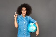 Idea for travel. Mulatto woman standing isolated on grey with terrestrial globe pointing up smiling excited royalty free stock images