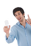 Idea - Young man holding energy saving light bulb Royalty Free Stock Photo