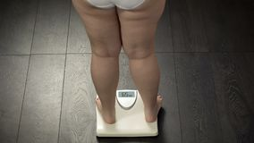 Ideaal lichaamsgewicht, vrouw die zich op schalen bevinden om het op dieet zijn resultaat, achtergedeelte te meten stock foto