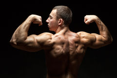 Ideal beautiful back muscles in men. Man back to us in his perfect beautiful muscles of the back, it on a black background Royalty Free Stock Images