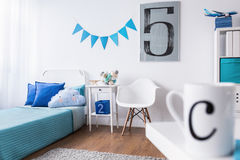 Ideal bedroom for little boy. Perfect designed bedroom with white walls, wooden floor and blue elements ideal for boy Royalty Free Stock Image