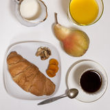 The ideal breakfast for the proper energy for the whole day. Coffee, orange juice, fruit and croissant. Royalty Free Stock Photos