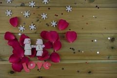Romantic winter season photography image with marshmallows shaped as snowman with smiles iced on laying in red rose petals Stock Photography