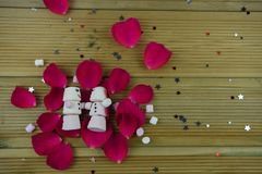 Romantic winter season photography image with marshmallows shaped as sleeping snowman with smiles iced on lying in red rose petals Stock Photo