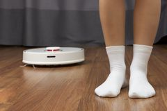 Ideal cleanliness. Women`s feet. In white socks and robot vacuum cleaner stock photo