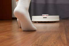 Ideal cleanliness. Women`s feet in white socks. And robot vacuum cleaner stock photo