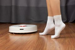 Ideal cleanliness. Women`s feet in white socks. And robot vacuum cleaner royalty free stock images
