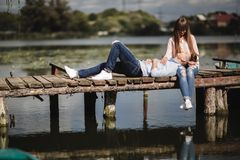 Ideal moment.. Beautiful young couple embracing and smiling while sitting on the pier. Perfect date. Beautiful young couple embracing and smiling while sitting stock images
