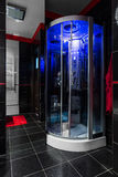 Ideal place for a relaxing shower. Black bathroom with hydromassage shower and blue led lighting Royalty Free Stock Photography