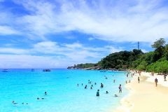 Ideal relaxed beach holiday in a tropical resort. Similan Islands, Thailand - March 31, 2017: tourists rest on a sandy beach with azure sea water. On the shore Stock Photography