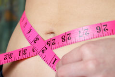 Ideal Waistline. A woman measures her waistline to account for her ideal size and fitness royalty free stock photography